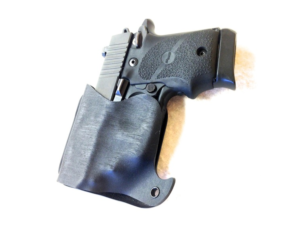 a custom kydex pocket gun holster is in a sheath in a jeans pocket